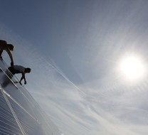 Construction workers fix solar panels for solar power plant near Olching